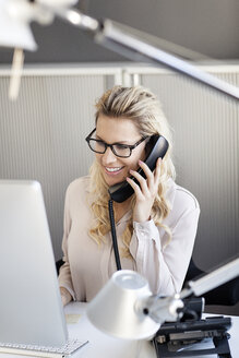 Smiling blond woman in office on the phone - PESF000070