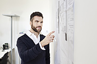 Man in office pointing at wall with papers - PESF000079