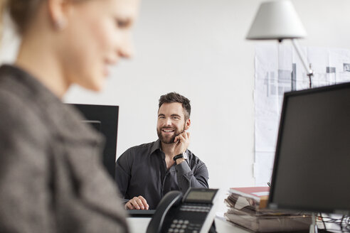 Man in office looking at woman - PESF000090
