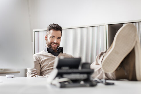 Man in office laying his feet on desk - PESF000092
