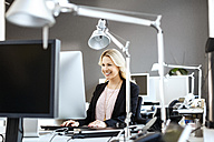 Smiling blond woman working at desk in office - PESF000105