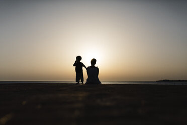 Spain, Menorca, silhouette of mother and son watching the sunset at seafront - JRFF000009