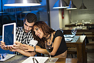 Young couple in modern restaurant taking a selfie with digital tablet - JASF000009