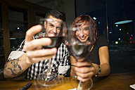 Happy young couple in a restaurant toasting with red wine glasses to the viewer - JASF000011