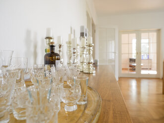 Collection of old crystal glasses on wooden sideboard in a modern apartment - LAF001480