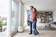 Couple in living room looking out of window - RBF003554