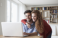 Happy couple at home looking at laptop - RBF003504