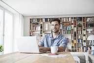 Portrait of smiling man at home using laptop - RBF003557