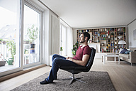 Man at home sitting in armchair looking out of window - RBF003561