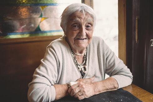Portrait of smiling senior woman sitting in a restaurant - RAEF000364