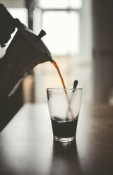 Man pouring espresso from can into a glass - RAEF000384
