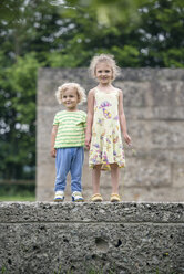 Portrait of little sister and brother standing side by side on a wall holding hands - OPF000073