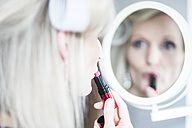 Blond woman with curlers applying lipstick - CHPF000162