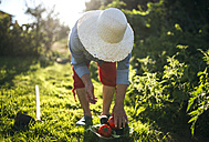 Senior woman with straw hat working in her garden - MGOF000511