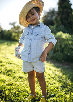 Portrait of smiling little girl wearing straw hat standing in a garden - MGOF000513