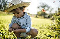 Little girl wearing straw hat crouching on a meadow - MGOF000519