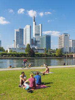 Germany, Hesse, Frankfurt, People at River Main with skyline in background - AM004149