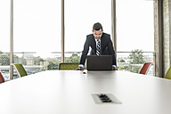 Young businessman in conference room looking at laptop - UUF005415