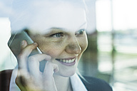 Smiling young businesswoman behind windowpane on cell phone - UUF005429