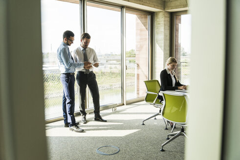Two businessmen with digital tablet and businesswoman in conference room - UUF005439