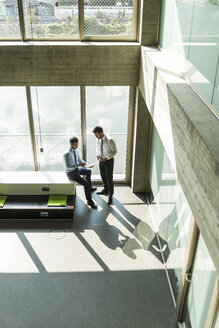 Two young businessmen discussing documents - UUF005477