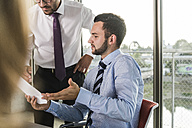 Business people discussing document in office - UUF005505