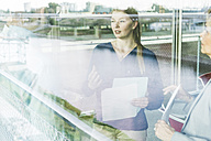 Business people with documents talking behind window pane - UUF005514