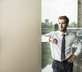 Serious young businessman leaning against column - UUF005521