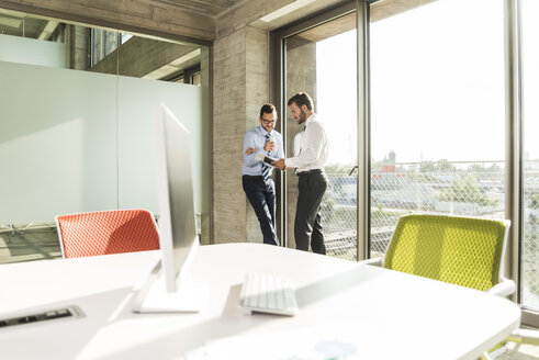 Two young businessmen talking at the window in office - UUF005550
