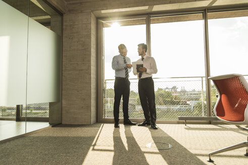 Two young businessmen talking at the window in office - UUF005556