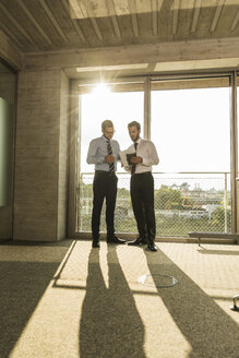 Two young businessmen talking at the window in office - UUF005552