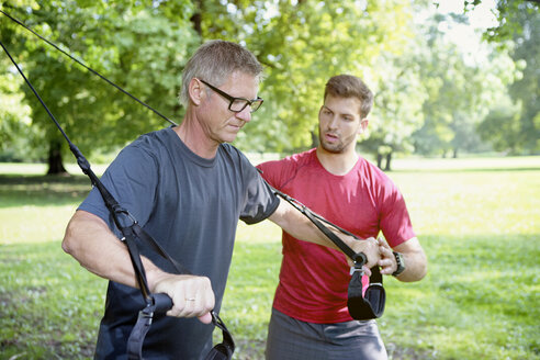 Man doing TRX training while his personal trainer watching him - SEGF000407