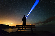 Spain, Ortigueira, Loiba, silhouette of a man standing on bench under starry sky with blue ray - RAEF000391