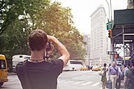 USA, New York City, Tourist taking pictures of Flatiron Building - ONF000880