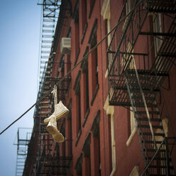USA, New York City, SoHo, Trainers hanging on electric cable - ONF000907