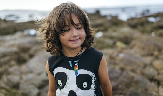 Spain, Gijon, portrait of smiling little boy at rocky coast - MGOF000532