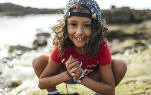 Spain, Gijon, portrait of smiling little girl crouching at rocky coast - MGOF000533
