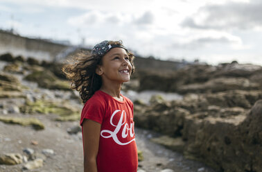 Spain, Gijon, portrait of smiling little girl on rocky beach looking up - MGOF000536