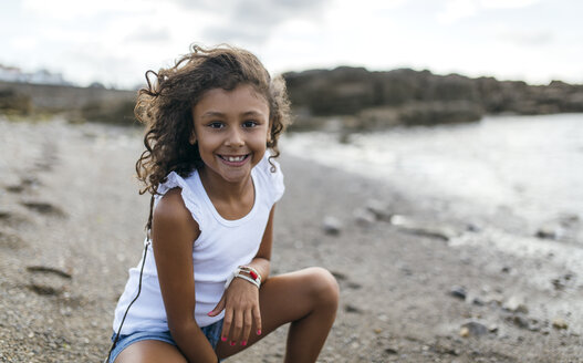 Spain, Gijon, portrait of smiling little girl crouching on the beach - MGOF000538