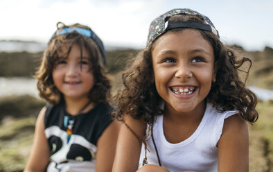 Spain, Gijon, portrait of smiling little girl and her friend in the background sitting at rocky coast - MGOF000542
