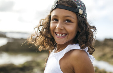 Spain, Gijon, portrait of smiling little girl with tooth gap at rocky coast - MGOF000547