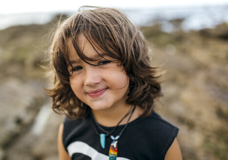 Spain, Gijon, portrait of smiling little boy with brown hair at rocky coast - MGOF000565