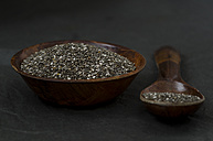 Wooden bowl and spoon of chia seeds on dark ground - ODF001225
