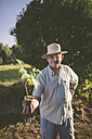Portrait of smiling farmer wearing straw hat holding potted plant in his hand - RAEF000403