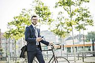 Young businessman pushing bicycle, holding smart phone - UUF005563