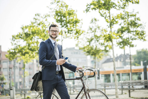 Young businessman pushing bicycle, holding smart phone - UUF005563