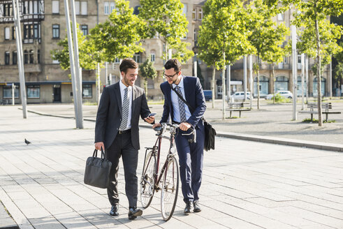 Two businessmen with bike and smart phone walking in the city - UUF005567
