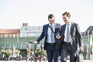 Two young businessmen walking in city, pushing bicycle - UUF005571