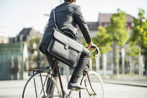 Young businessman riding bicycle - UUF005574