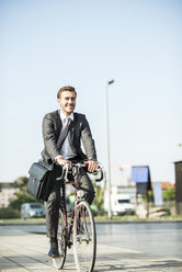 Young businessman riding bicycle - UUF005575